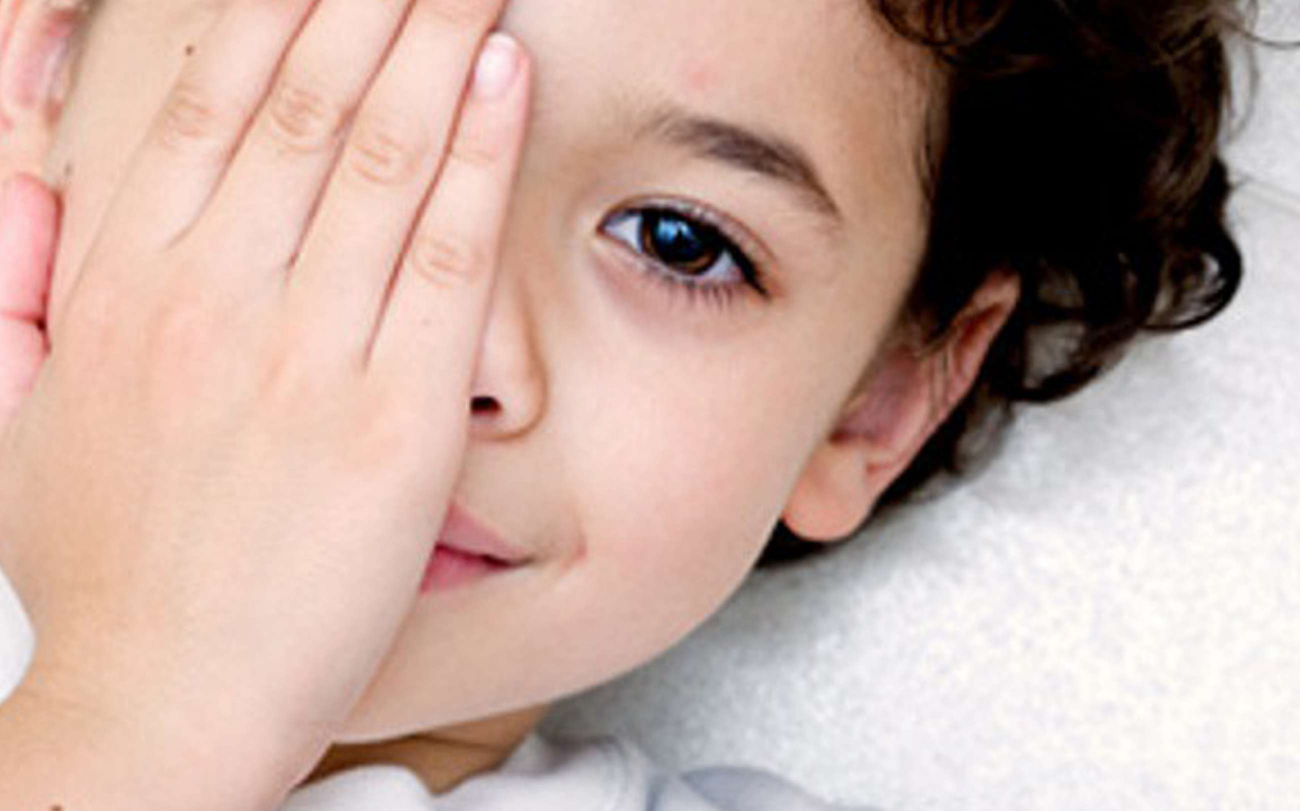 Child covering one eye with amblyopia